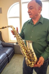 Tim Price talks about one of his saxophones. Dean Hare/Daily News