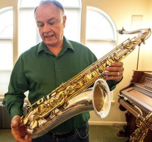 Tim Price talks about the engraving on this saxophone, which depict New York city scenes, including a skyline showing the Twin Towers. After the 9/11 terrorist attacks, the saxophone maker no longer uses those images on the instruments he makes. Dean Hare/Daily News