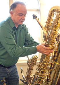 Tim Price picks up his bass saxophone while talking about his collection. Dean Hare/Daily News